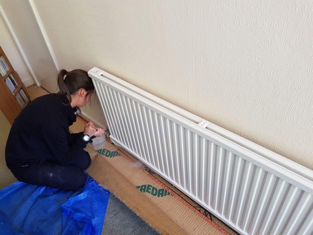 female plumber, central heating, radiator installation
